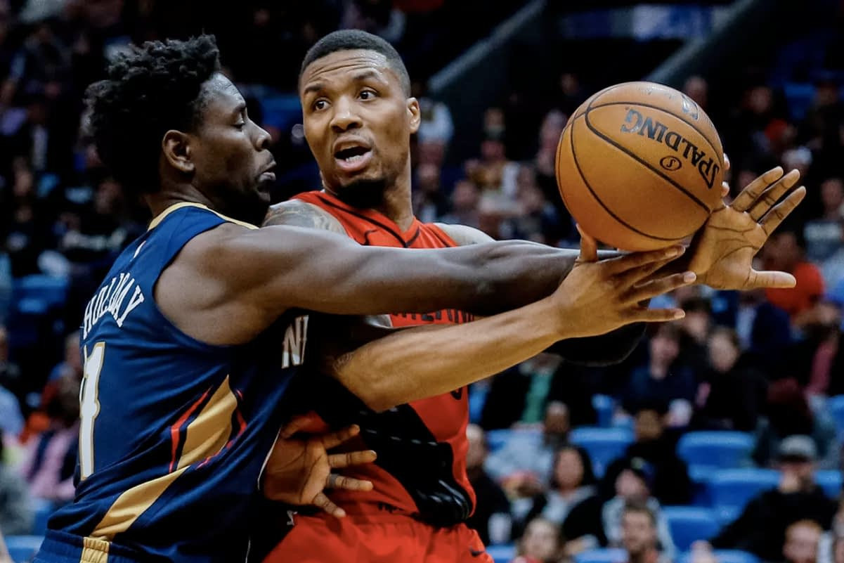 Damian Lillard guarded by Jrue Holiday