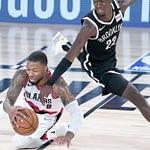 Damian Lillard swipes the basketball from Caris LeVert